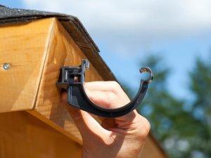 Ein Dachrinnenhalter anthrazit auf einem Distanzkeile.